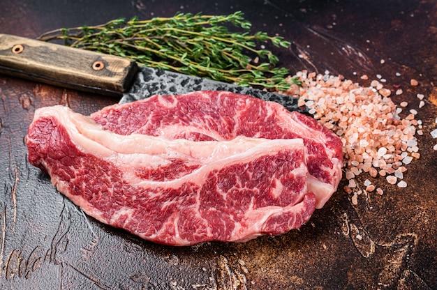 도살용 식칼에 블랙 앵거스 쇠고기 스테이크 생 스트립로인 또는 뉴욕을 얹습니다. 어두운 배경입니다. 평면도.