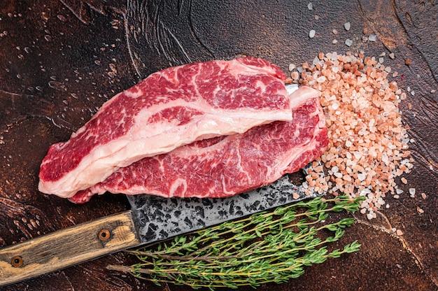 Прайм стейки из говядины блэк ангус сырой стриплойн или нью-йорк на мясорубке. темный фон. вид сверху.