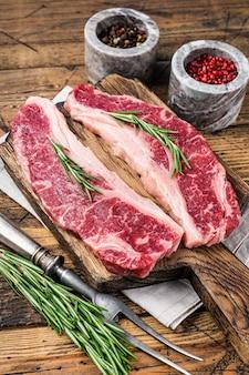 프라임 블랙 앵거스 쇠고기 스테이크 생 스트립로인 또는 뉴욕. 나무 배경입니다. 평면도.