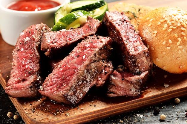 Prime black angus steak burger near bun and sauce