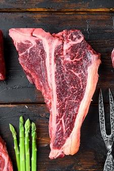 Нежный сырой стейк на косточке prime cut для набора для барбекю, на фоне старого темного деревянного стола, плоская планировка, вид сверху