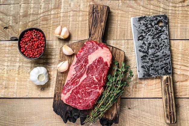 나무 테이블에 칼으로 정육점 나무 절단 보드에 갈비뼈 원시 쇠고기 고기 스테이크를 프라임. 평면도.
