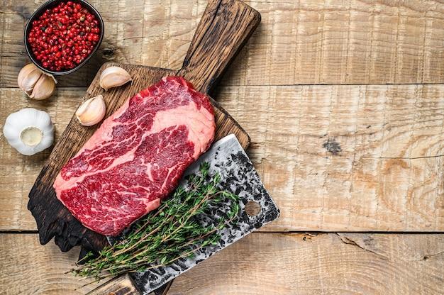칼으로 정육점 나무 커팅 보드에 갈비뼈 원시 쇠고기 고기 스테이크를 프라임. 나무 배경입니다. 평면도. 공간을 복사하십시오.
