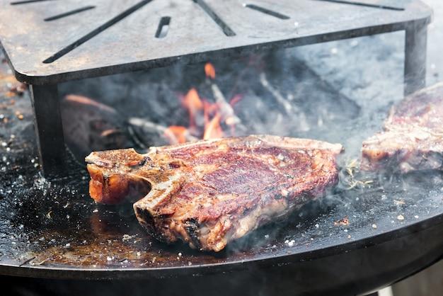 뜨거운 바베큐 불에 지글지글 끓는 프라임 립 또는 즙이 많은 쇠고기 스테이크와 함께 야외 철판
