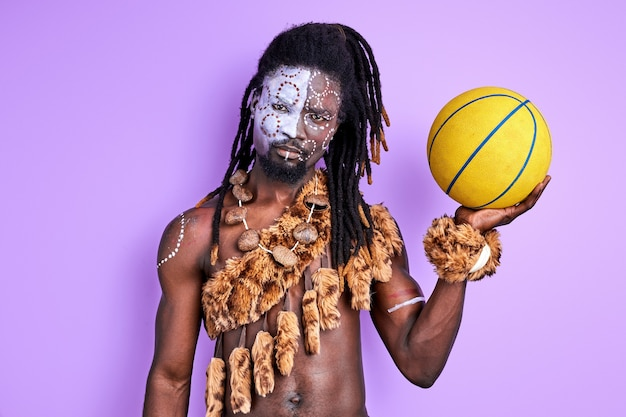 Primitive man in national authentic wear holding yellow ball in hands, going to play basketball