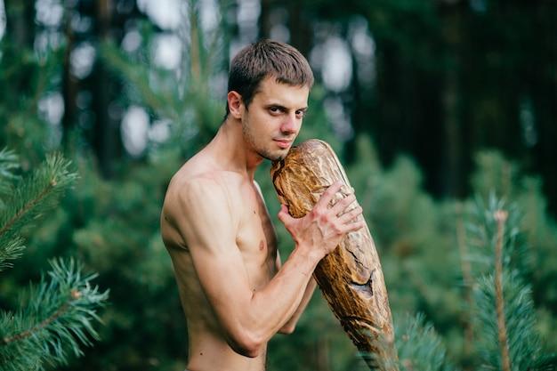 森でポーズをとって巨大な木製の棒で原始的な裸の男