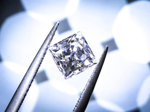 Princess diamonds cut. in the tweezers  on bokeh background.