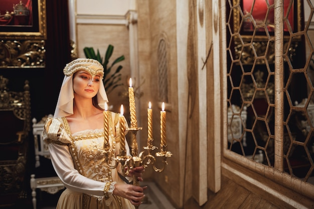 Princess in golden clothes carries candleholder with burning candles