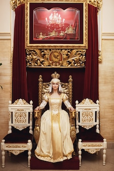 Princess in rich golden dress sits on the throne before red wall