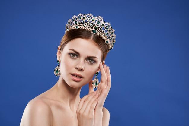 그녀의 머리 메이크업 모델 손 제스처 파란색 배경에 왕관과 함께 공주. 고품질 사진
