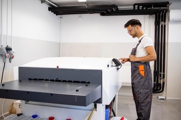 인쇄소에서 기계를 인쇄하기 위해 컴퓨터를 작동하는 작업자를 인쇄합니다. 프리미엄 사진
