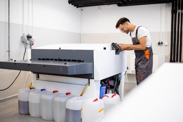 인쇄소에서 기계를 인쇄하기 위해 컴퓨터를 작동하는 작업자를 인쇄합니다.
