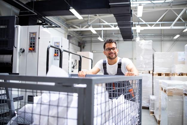 Работник типографии перемещает использованные листы бумаги на фабрике типографии.