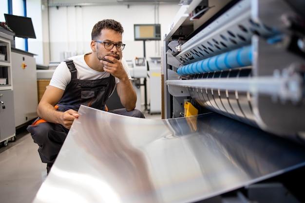 인쇄소에서 컴퓨터에 인쇄하는 기계의 문제를 해결하려고 하는 인쇄 작업자.