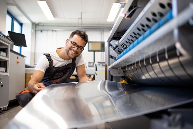 인쇄소에서 인쇄 기계에 컴퓨터 작업을 하는 인쇄 작업자.