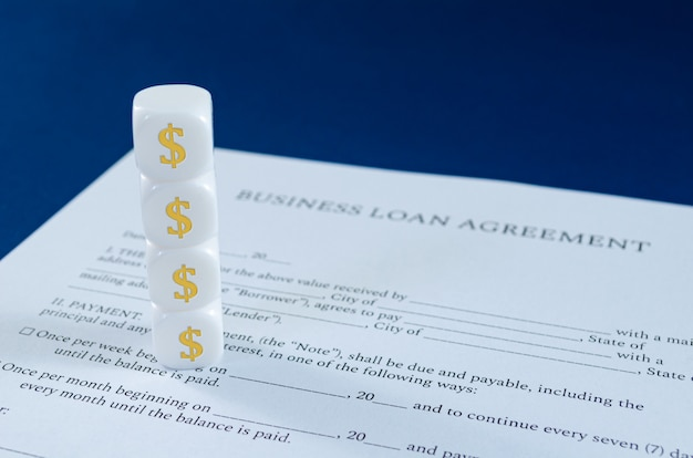 Printed business loan agreement with column of white blocks with golden dollar signs in a conceptual image. over blue space.