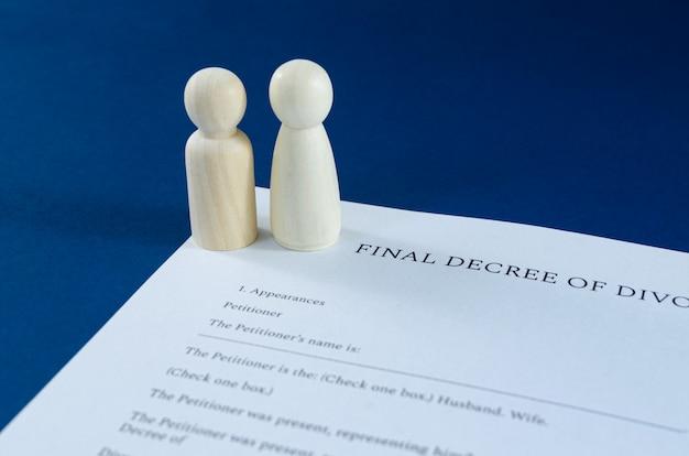 離婚の概念的なイメージで男性と女性の木造人物との離婚の印刷されたdecre。青い空間の上。