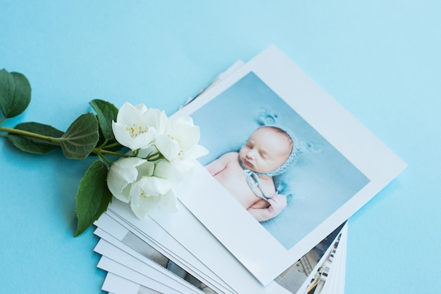 Printed photos, frame cards, on a blue background with a white flower.  family photo
