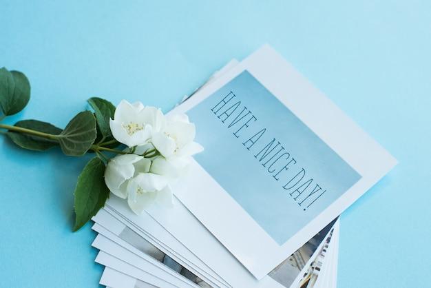 Распечатанные фотографии, открытки в рамке, на синем фоне с белым цветком. макет.