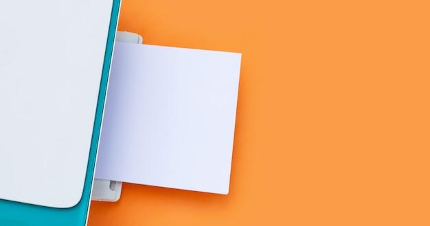 프린터와 오렌지 배경에 종이입니다.