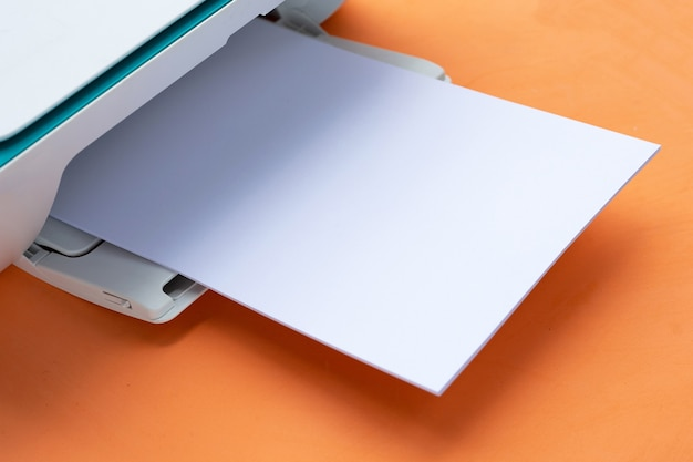 Printer and paper on orange background.