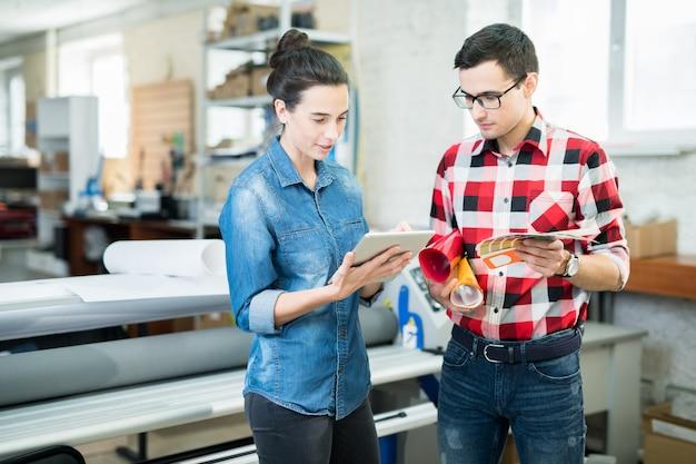 디자인과 종이를 논의하는 인쇄 전문가
