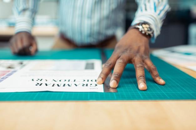 ポスターの印刷。ポスターの印刷に取り組んでいるハンドウォッチを身に着けている浅黒い肌の男のクローズアップ