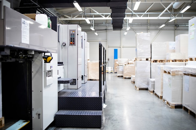 Printing shop interior with modern offset paper machine and piles of sheets in background
