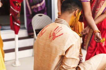 Prints of red palms put over the shirt of Indian groom sitting