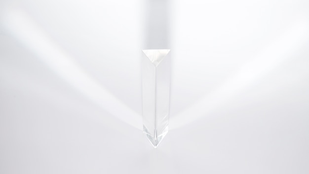A prism dispersing sunlight on a white background