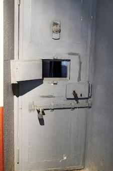 観察窓とスチールボルト付きの刑務所の独房の鉄の扉。金属製の刑務所のドア