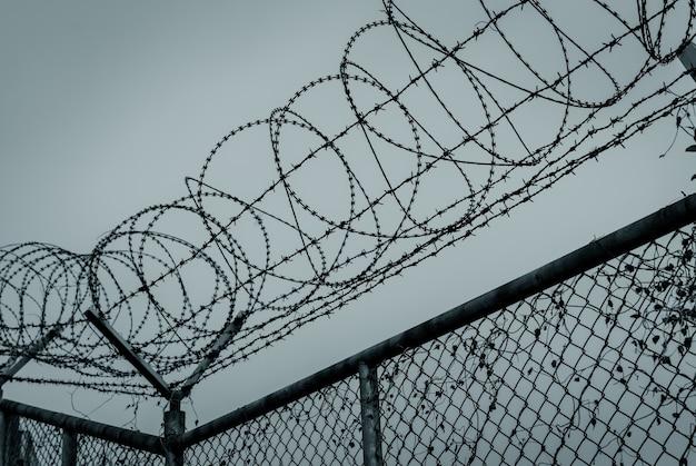 감옥 보안 울타리입니다. 철조망 보안 울타리. 면도날 철사 감옥 울타리. 장벽 경계. 경계 보안 벽. 범죄자나 테러리스트를 체포하기 위한 감옥. 개인 공간. 군사 구역 개념입니다.