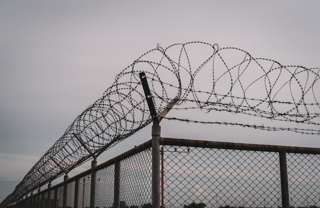Забор тюремной безопасности. ограждение из колючей проволоки. забор тюрьмы из колючей проволоки. барьерная граница. пограничная стена безопасности. тюрьма для ареста преступников или террористов. частная территория. концепция военной зоны.