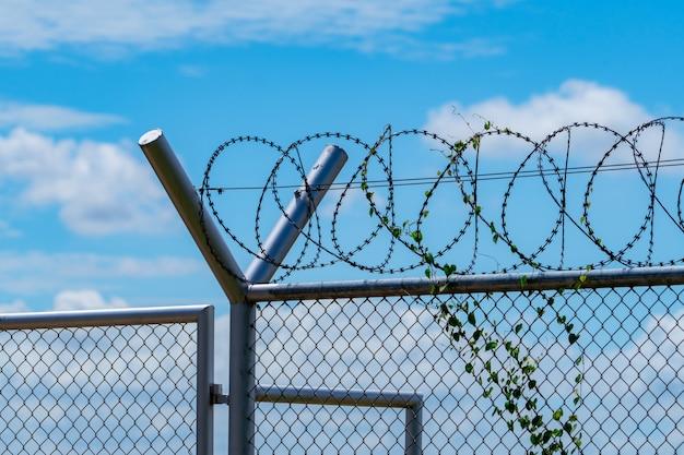 Забор тюремной безопасности. ограждение из колючей проволоки. забор тюрьмы из колючей проволоки. барьерная граница.