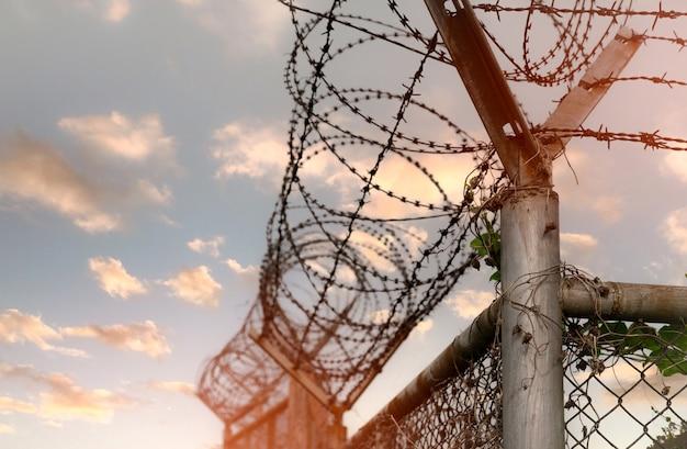 감옥 보안 울타리 철조망 보안 울타리 면도기 철사 감옥 울타리 장벽 국경 프리미엄 사진