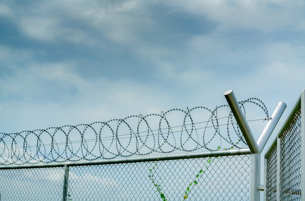 Prison security fence. barbed wire security fence. razor wire jail fence.