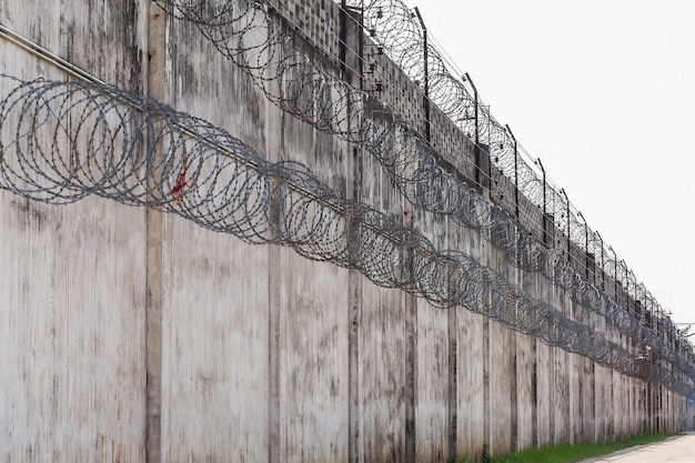 Prison walls, fence with barbed wire.