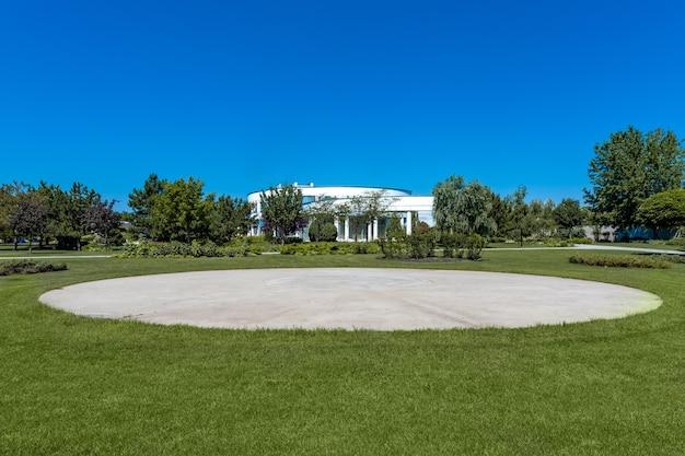 夏の日の豪華なカントリーハウスの背景に緑の芝生の上のプライベートヘリポート