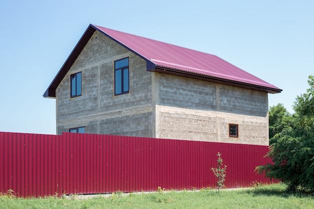 울타리 뒤에 창문과 지붕이 있는 건설 중인 개인 주택. 시골집.