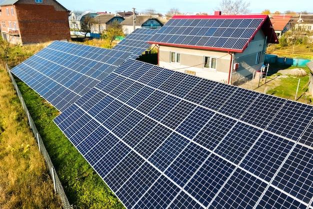Частный дом с расположенными на земле солнечными фотоэлектрическими панелями для производства чистой электроэнергии.