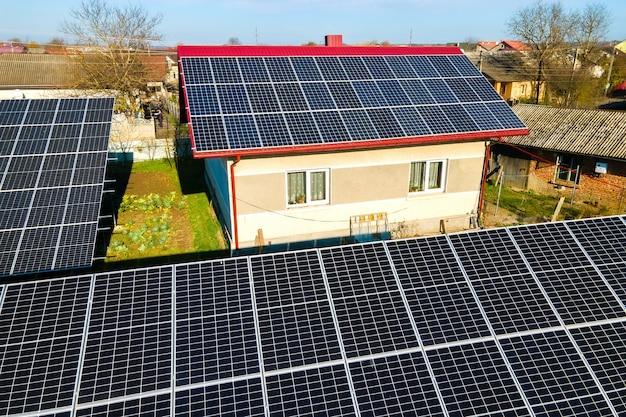 Частный дом с расположенными на земле солнечными фотоэлектрическими панелями