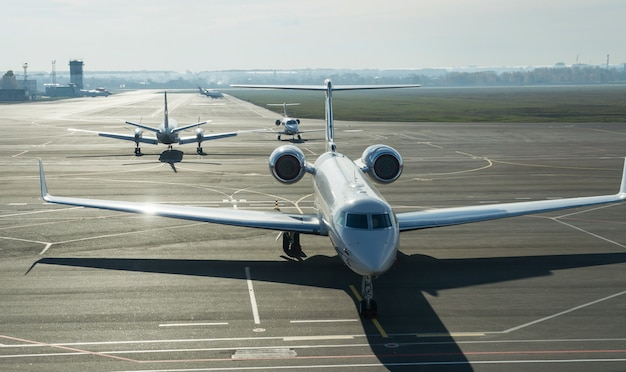 Private jet planes stand on the landing line.
