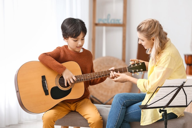 Private music teacher giving guitar lessons to little boy at home