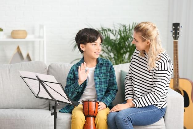 自宅で小さな男の子にレッスンを与えるプライベート音楽教師