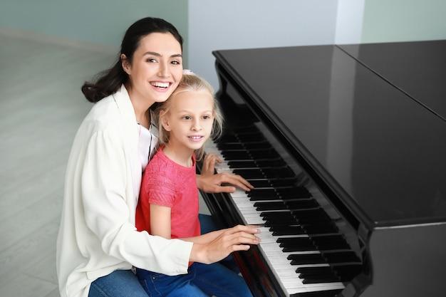 Частный учитель музыки дает уроки игры на фортепиано маленькой девочке