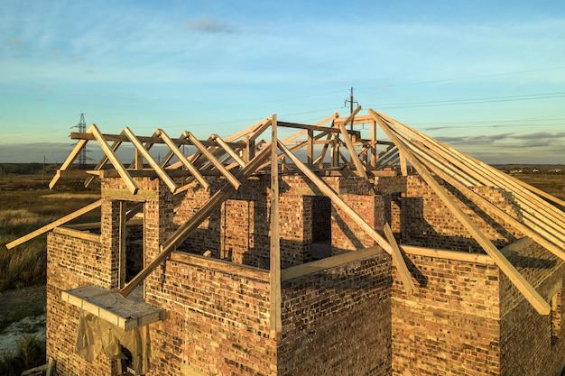 Строящийся частный жилой дом с деревянной крышей каркасной конструкции. незавершенный кирпичный дом под застройку.