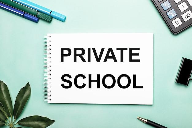 Частная школа написана на белом листе на синем фоне рядом с канцелярскими принадлежностями и листом шеффлера.