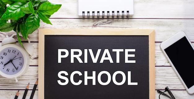 鉛筆、スマートフォン、白いメモ帳、鉢植えの緑の植物の近くの黒い背景に書かれた私立学校