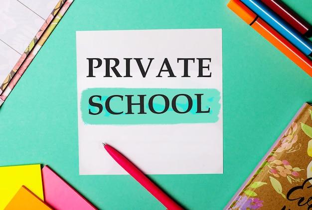 Частная школа написано на бирюзовом фоне рядом с яркими наклейками, блокнотами и фломастерами