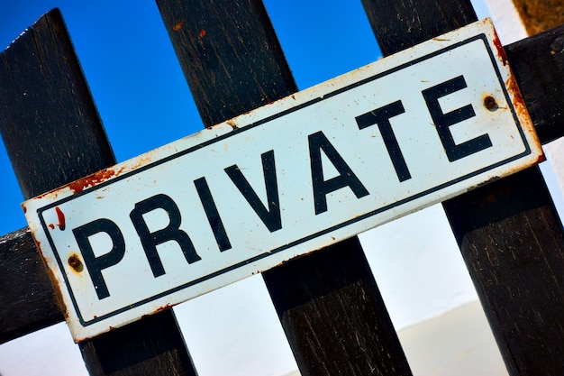 Private sign on a wooden gate close-up
